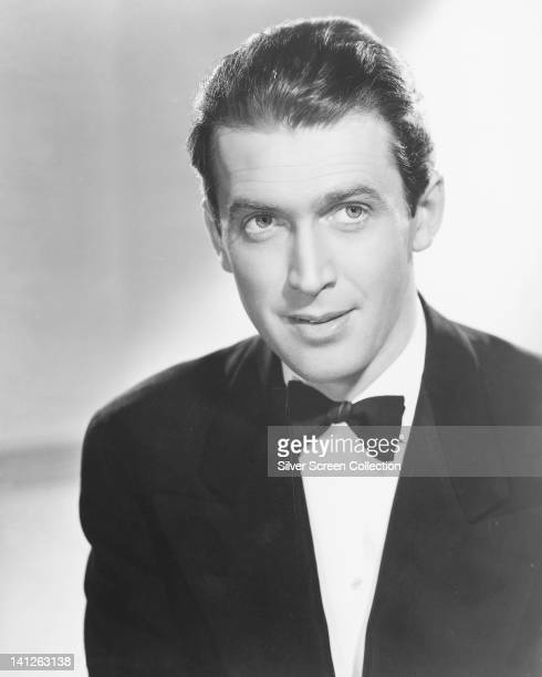 Headshot of James Stewart US actor wearing a black dinner jacket a white shirt and a black bow tie in a studio portrait against a white background...