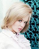 Headshot of Joey Heatherton US actress dancer and singer wearing a light pink blouse posing before blue ornamental metalwork circa 1965