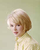 Headshot of Joey Heatherton US actress dancer and singer wearing a yellow and white check blouse in a studio portrait against a yellow background...