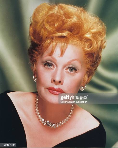Headshot of Lucille Ball US comedian and actress wearing pearl earrings and a pearl necklace in a studio portrait against a green background circa...