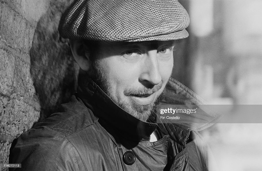 Headshot of Richard Thompson, British singer-songwriter and guitarist, wearing a flat cap and overcoat while posing against a bare brick wall for a portrait at Rufus Street Studios, on Rufus Street, London, England, Great Britain, in July 1986.