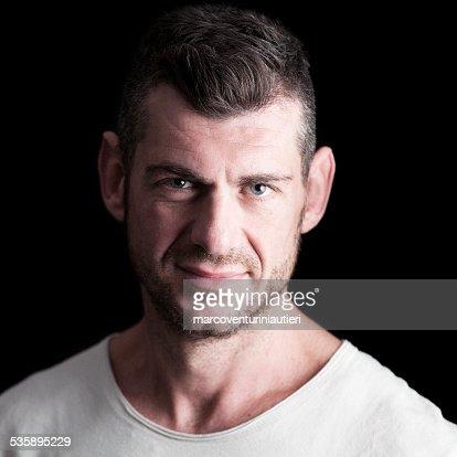 Headshot of serene man in white t-shirt, black background