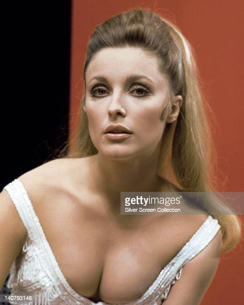 Headshot of Sharon Tate US actress wearing a white low cut top in a studio portrait against a red and black background circa 1965