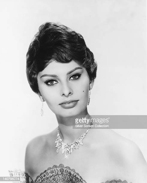 Headshot of Sophia Loren Italian actress looking glamorous wearing a shoulderless dress and a diamond necklace and diamond earrings in a studio...