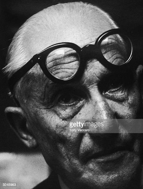 Headshot of Swiss architect Le Corbusier wearing his eyeglasses on his forehead Paris France