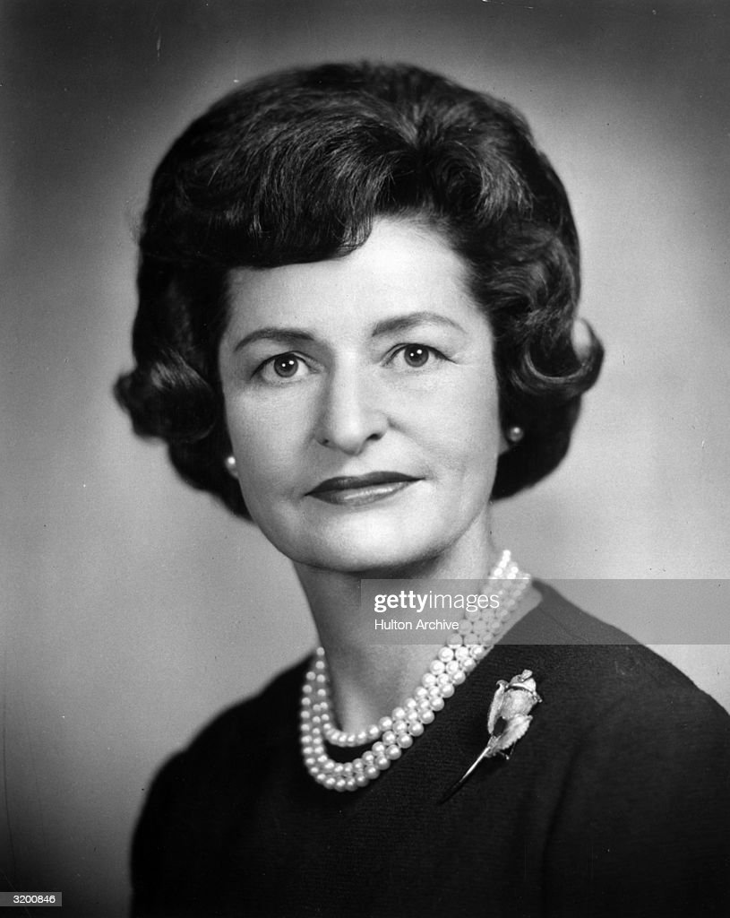 Headshot of Vice President Lyndon B. Johnson's wife, Lady Bird, wearing a pearl necklace and a rose brooch on her sweater.
