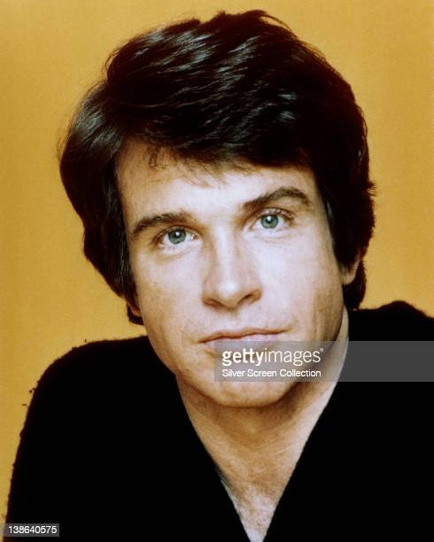 Headshot of Warren Beatty US actor in a studio portrait against a yellow background circa 1965
