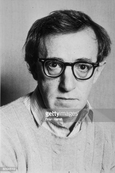 Headshot portrait of American actor and director Woody Allen wearing a sweater over a shirt and hornrimmed glasses on the set of his film 'Hannah and...