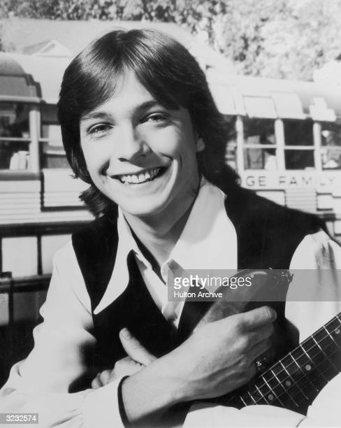 Headshot portrait of American pop musician and actor David Cassidy smiling and holding a guitar