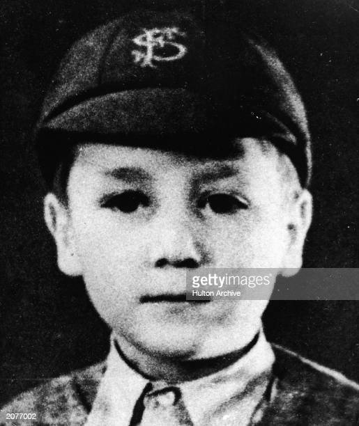 Headshot portrait of British musician and songwriter John Lennon of the pop group The Beatles as a young boy in a school uniform and cap c 1948