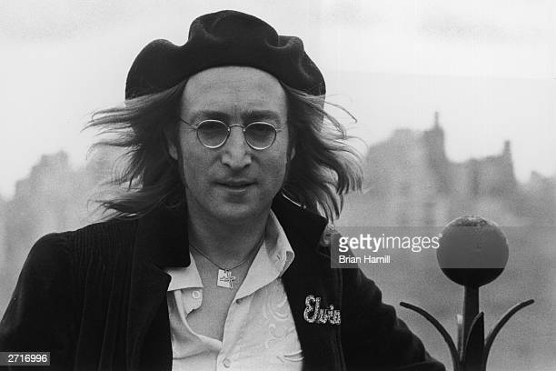 Headshot portrait of British rock singer and songwriter John Lennon standing on the roof of his apartment building the Dakota New York City He wears...
