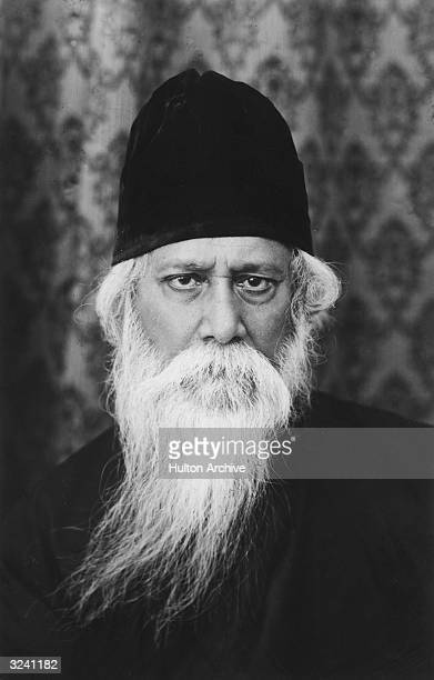 Headshot portrait of Indian poet and philosopher Rabindranath Tagore dressed in a black cap and cape