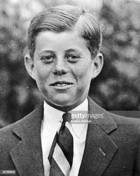 Headshot portrait of John F Kennedy at age ten standing outdoors and wearing a suit with his hair slicked back