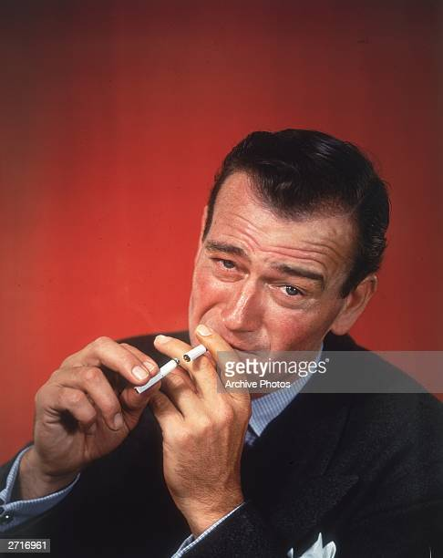 Headshot studio portrait of American actor John Wayne in front of a red background dressed in a sport coat lighting a cigarette with an already lit...