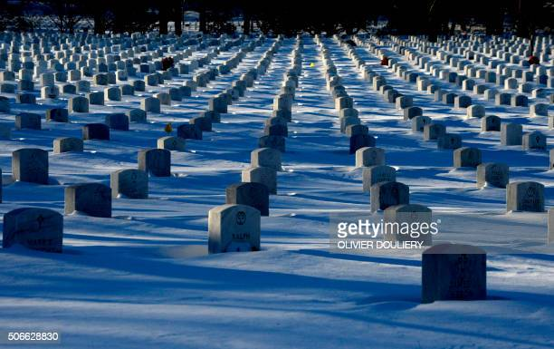 Headstones are nearly covered by snow at Arlington National Cemetery in Washington on january 24 2016 Millions of people in the eastern United States...