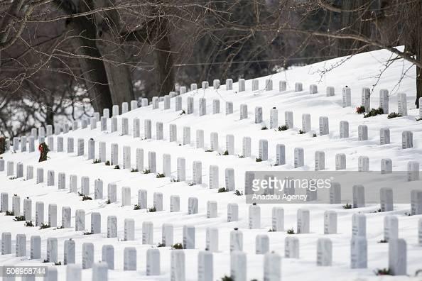 Headstones poke up from the snow in Arlington National Cemetery in Arlington Va USA on January 26 2015 The Washington region is still recovering from...