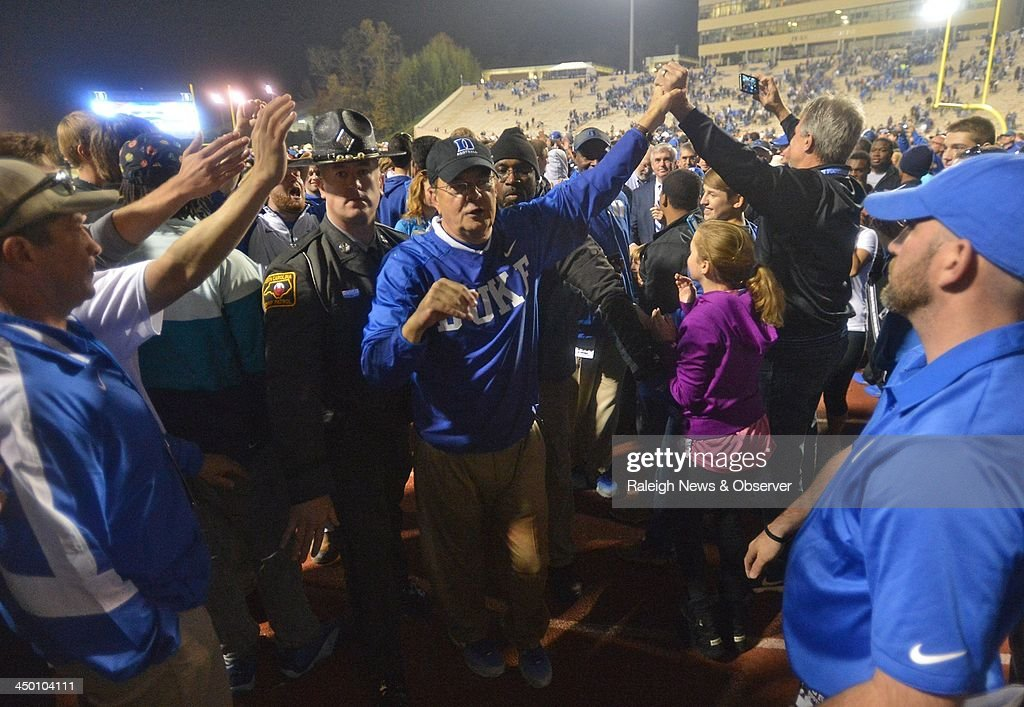 Heaed Coach David Cutcliffe of Duke is mobbed as he heads to the locker room. The Duke Blue Devils defeated the Miami Hurricanes, 48-30, at Wallace Wade Stadium in Durham, N.C., on Saturday, Nov. 16, 2013.