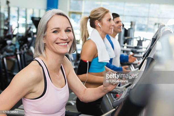 Healhty mature woman walking on treadmill in gym
