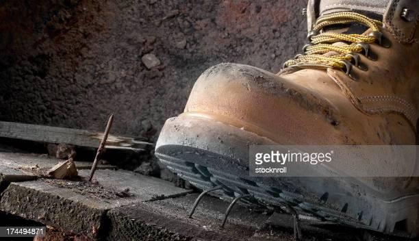 Gesundheit und Sicherheit schmutzig Arbeitsstiefel Schritt an einem Nagel