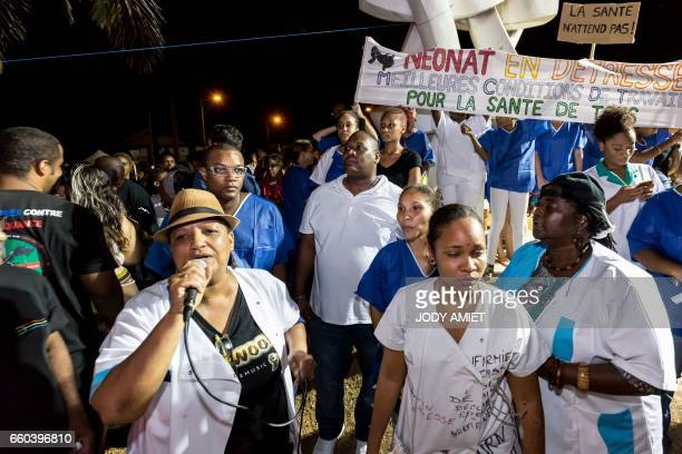 Health care personnel form the Cayenne hospital take part in a protest gathering at a blockade on March 29 2017 in Cayenne holding a banner reading...