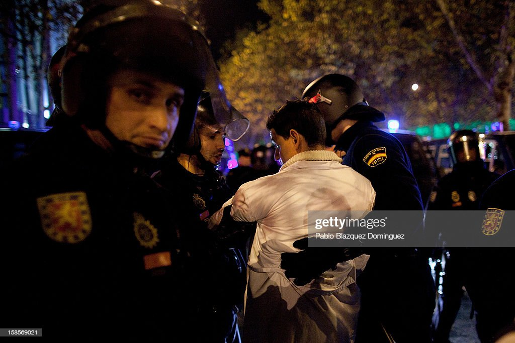 A health care worker is grabbed by riot police during a demonstration outside Madrid Regional Asembly on December 19, 2012 in Madrid, Spain. All health workers unions are calling for a third 48 hour strike starting today, against cuts on public health care and the privatization of medical centers and hospitals.