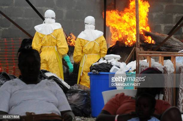 Health care workers wearing full body suits burn infected items at the Elwa hospital run by Medecins Sans Frontieres in Monrovia on August 30 2014...