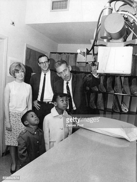 Health Center Year Old Frank Justice administrator of the Denver Neighborhood Health Center shows Xray equipment to Nathan Howell Jr and Jacqueline...