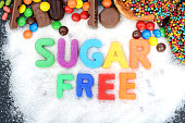 "Health concept with multicolored letter blocks on granulated white sugar spelling ""sugar free"""
