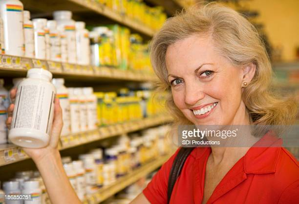 Health Conscious Shopper Checking Vitamin Bottle at the Store