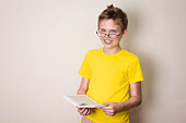 Health, education and people concept. Happy teen boy in braces and eyeglasses holding a book and smiling.