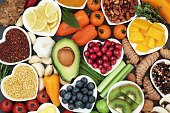 Health food for fitness concept with fresh fruit, vegetables, pulses, herbs, spices, nuts, grains and pulses. High in anthocyanins, antioxidants,smart carbohydrates, omega 3 fatty acids,  minerals and
