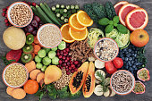 Health food concept for a high fiber diet with fruit, vegetables, cereals, whole wheat pasta, grains, legumes and herbs. Foods high in anthocyanins, antioxidants, smart carbohydrates and vitamins on m