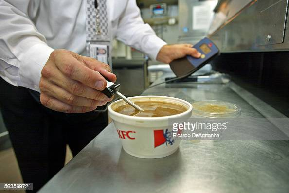 Health inspector Richard Lavin checking the temperature of gravy during inspection at Kentucky Fried Chicken restaurants on 6th St