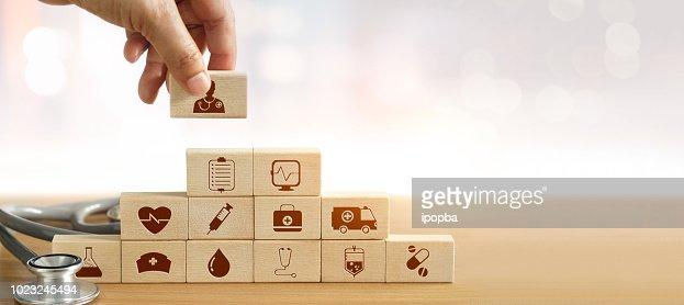 Concept d'assurance-maladie, main de docteur en médecine tenant la cale en bois et empiler les soins médicaux icône et stéthoscope sur fond. : Photo