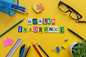 Health Insurance - word of carved letters at office workplace insurance agent.