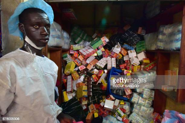 Health Ministry employee takes part in an operation to empty shops selling fake medicine during a raid monitored by police officers against shops...