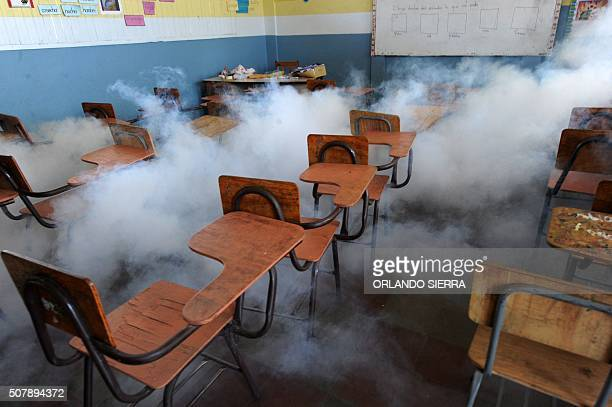 Health ministry personnel fumigate a classroom against the Aedes aegypti mosquito vector of the dengue Chikungunya and Zika viruses in Tegucigalpa on...