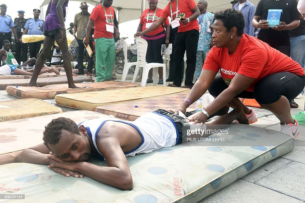 Health official attends to Ethiopian marathoner Tamru Makonnen after the first Lagos City Marathon, on February 6, 2016 in Lagos. / AFP / PIUS UTOMI EKPEI