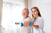 Health visitor and a senior man during home visit. A nurse or a physiotherapist helping a senior man exercise with dumbbells.