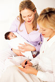 Health visitor filling out form for mother holding new born baby