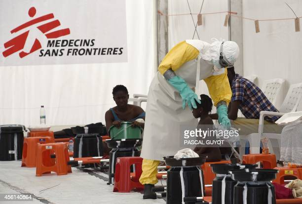 A health worker attends to a girl at the medical centre of Doctor Without Borders Medecin sans Frontiere where people infected with the Ebola virus...