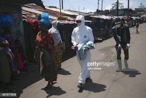 A health worker carries Benson 2 months to a reopened Ebola holding center in the West Point neighborhood on October 17 2014 in Monrovia Liberia The...