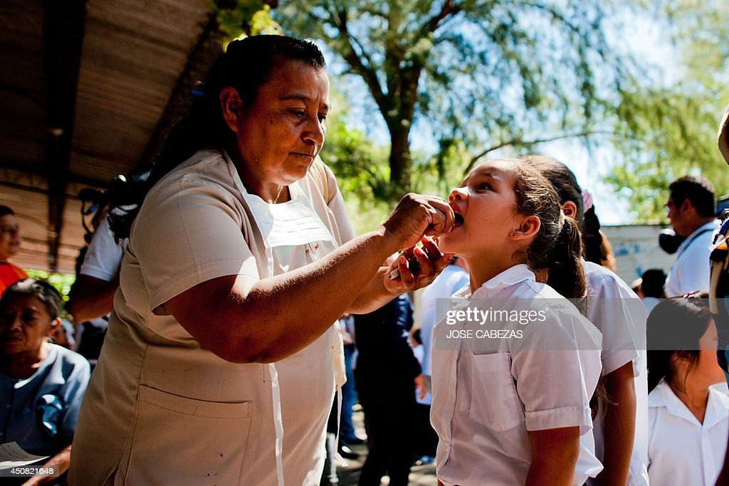 A health worker examines a patient during a medical brigade to detect suspicious cases of Chikungunya fever in a school of the town of Ayutuxtepeque, 4 km north of San Salvador, El Salvador on June 18, 2014. A Chikungunya fever outbreak was detected in some parts of El Salvador since last month, as the minister of health is working to control aedes aegipty mosquito. AFP PHOTO/ Jose CABEZAS