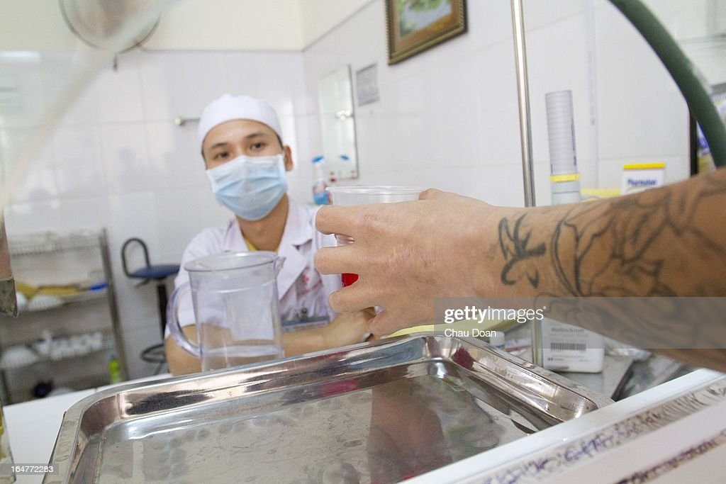 A health worker gives drug addicts their daily methadone dose at the Long Bien District Health Center. Vietnam has many comprehensive health programs aimed at the prevention of HIV and to help drug addicts. At this health center, there are comprehensive HIV services, including HIV testing, antiretroviral treatment, distribution of clean needles and condoms, and methadone maintenance therapy for drug addicts..