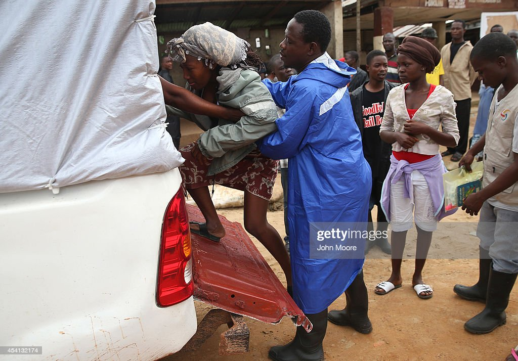 A health worker helps a sick girl onto a truck to be taken to the county clinic for observation for possible Ebola on August 24 2014 in Dolo Town...