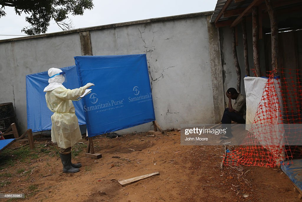 A health worker interviews a sick man after he arrived to a Ministry of Health treatment center for Ebola patients on October 2 2014 in Monrovia...