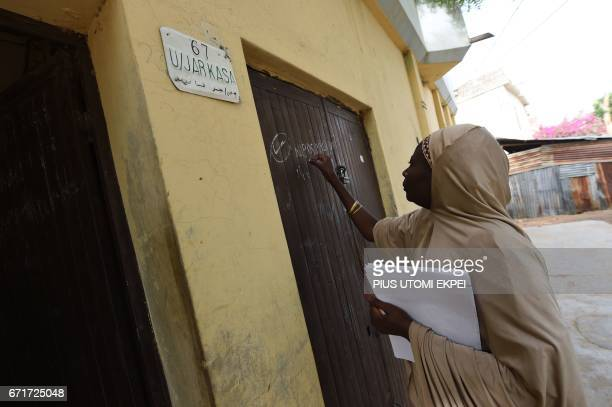 A health worker marks the gate of a house which was visited during a vaccination campaign against polio at HotoroKudu Nassarawa district of Kano in...