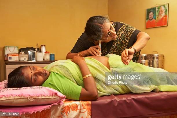 Health worker of NGO Chinmaya Organization of Rural Development CORD using fetal stethoscope on abdomen of pregnant woman