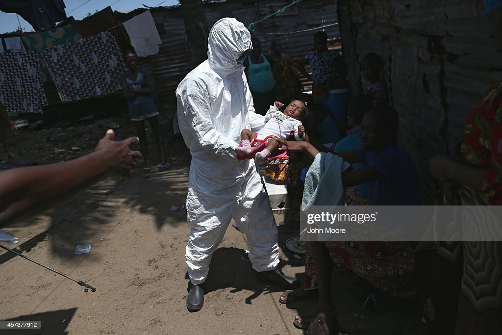 A health worker takes Benson 2 months from her mother to carry him to a reopened Ebola holding center in the West Point neighborhood on October 17...
