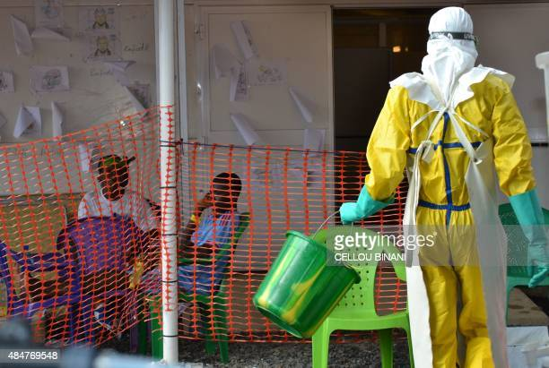 A health worker walks towards patients under quarantine at the Nongo ebola treatment centre in Conakry Guinea on August 21 2015 The World Health...